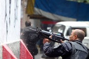 A policeman is seen during a shootout with traffickers during an operation at Vila Cruzeiro slum in Rio de Janeiro